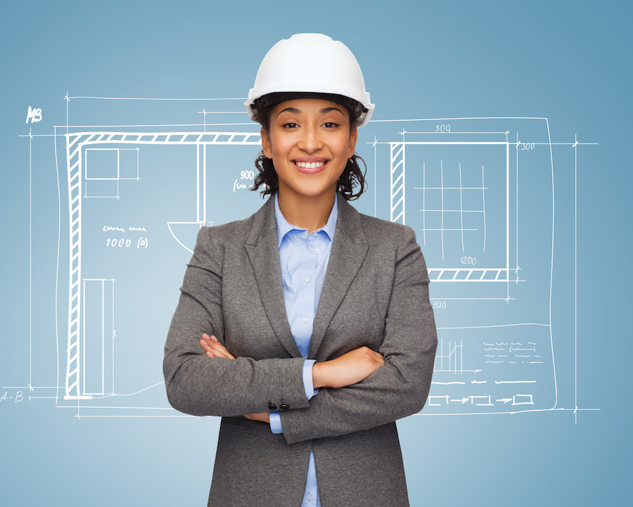 Woman in hard hat standing in front of blueprint